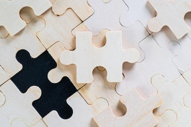 Schot van houten puzzelstukjes op zwarte achtergrond, bedrijfsconcept