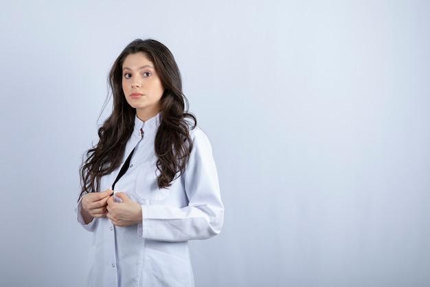 Schot van jonge dokter in witte jas staande op witte muur.