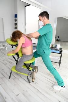 Schot van jonge fysiotherapeut die achterkant van zwangere vrouw masseren. man met beschermend gezichtsmasker tijdens nieuwe normaal.
