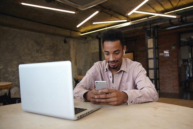 Schot van jonge knappe donkere huid freelancer met bebaarde zit over coworking space in vrijetijdskleding, op afstand werken met laptop, smartphone in handen houden en bericht typen