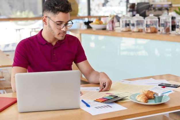 Schot van jonge man gebruikt laptopcomputer voor het controleren van de wisselkoers op internet, werkt met financiële documenten, laat stickers achter op sommige papieren, gaat lekker lunchen in gezellige snackbar