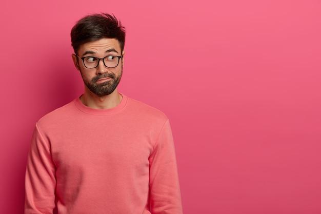Schot van knappe bedachtzame man met donkere dikke baard geconcentreerd opzij op lege ruimte van roze muur, merkt interessante scène op, heeft een verbaasde uitdrukking, draagt een transparante bril en trui