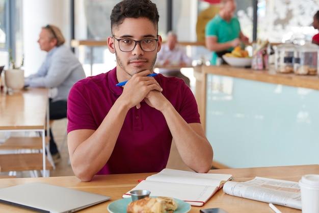 Schot van knappe ernstige gemengd ras jongeman schrijver houdt pen, maakt lijst te doen in kladblok, drinkt koffie, lunchtijd in coffeeshop alleen, bezig met werk.