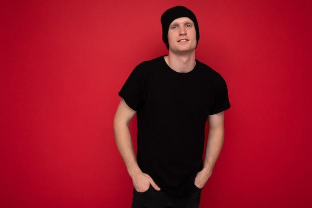 Schot van knappe gelukkig lachend jonge man permanent geïsoleerd op rode achtergrond muur dragen zwarte t