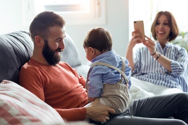 Schot van knappe jonge vader die met zijn baby speelt terwijl moeder thuis foto's van hen maakt op de bank.