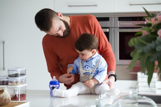 Schot van knappe jonge vader met zijn baby die thuis in de keuken speelt.
