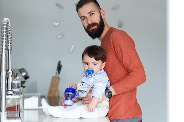 Schot van knappe jonge vader met zijn baby die thuis naar de camera in de keuken kijkt.