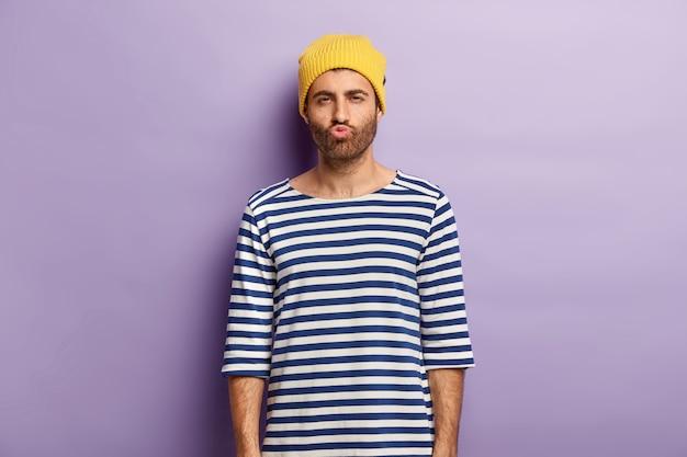 Schot van knappe jongere met borstelharen pruilt lippen en kijkt mysterieus, ontevreden over iets, draagt gele hoed en gestreepte zeeman trui