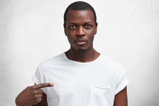 Schot van knappe serieuze jonge afrikaanse man met zelfverzekerde uitdrukking, geeft met wijsvinger op t-shirt aan voor uw logo of reclame-inhoud.