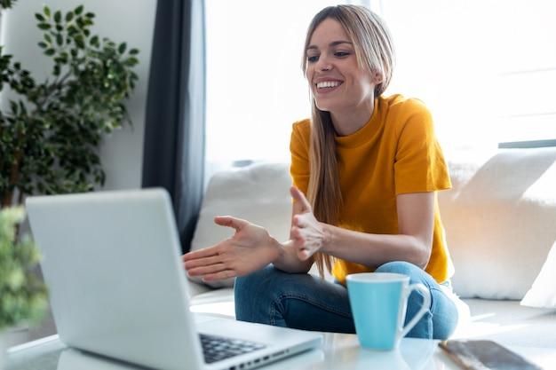 Schot van lachende jonge blonde vrouw met videogesprek op laptop zittend op de bank