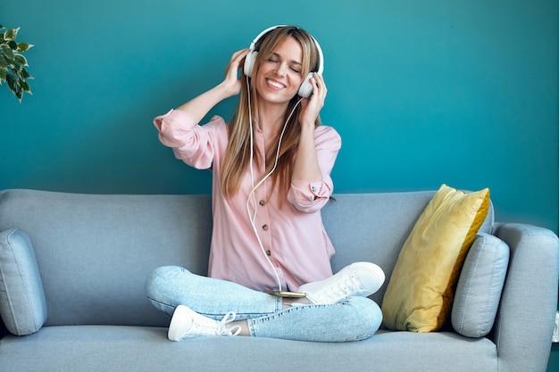 Schot van lachende jonge vrouw die naar muziek luistert met smartphone terwijl ze thuis op de bank zit.