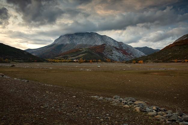Schot van land met zand aan de voorkant met rotsachtige bergen met lichte sneeuw