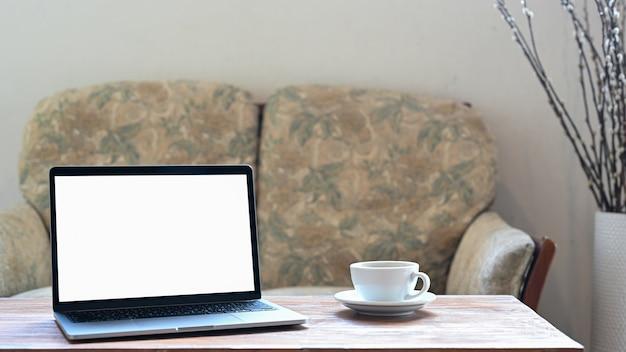 Schot van laptop mockup leeg scherm en witte koffiemok op houten tafel.