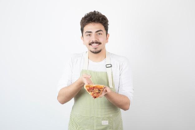 Schot van mannelijke kok die een stuk pizza op wit houdt