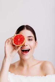 Schot van model met grijze ogen op geïsoleerde muur. positief meisje zonder make-up bedekt oog met halve grapefruit.
