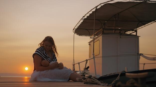 Schot van moeder met baby in kade bij zonsondergang. vrouw borstvoeding en strelen kind zittend op de pier in de buurt van vastgebonden boot. moederliefde en zorg