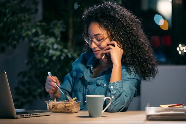 Schot van mooie afro jonge zakenvrouw die met de computer werkt terwijl ze pasta op kantoor eet.