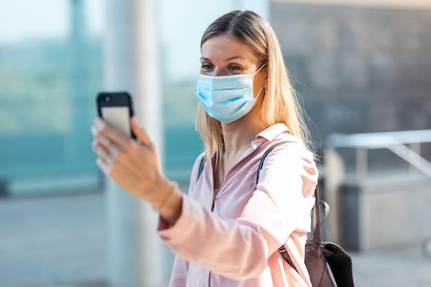 Schot van mooie blonde vrouw in gezichtsmasker die een selfie met smartphone op straat doet.