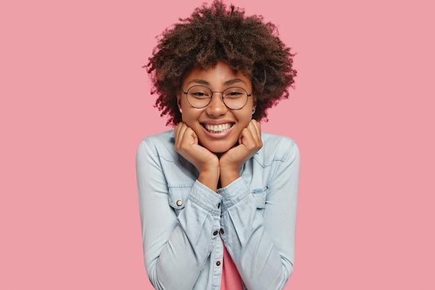 Schot van mooie gelukkige donkere huid vrouw heeft afro kapsel, breed glimlachen, toont witte perfecte tanden, blij om een compliment te ontvangen, gekleed in spijkerjasje, geïsoleerd over roze muur