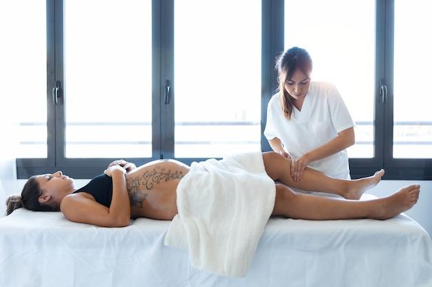 Schot van mooie jonge fysiotherapeut die de benen van de zwangere vrouw op een brancard thuis masseert.