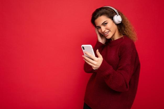 Schot van mooie jonge, gelukkige brunette krullende vrouw die een donkerrode trui draagt, geïsoleerd over rood