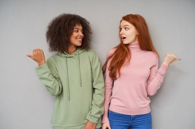 Schot van mooie jonge vriendinnen kijken elkaar terwijl poseren over grijze muur en tonen in verschillende richtingen met hun duimen, gekleed in vrijetijdskleding