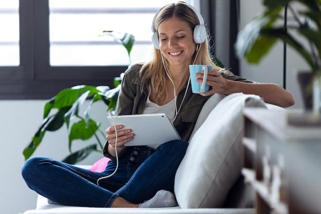 Schot van mooie jonge vrouw die naar muziek luistert met haar digitale tablet terwijl ze thuis een kopje koffie drinkt op de bank.