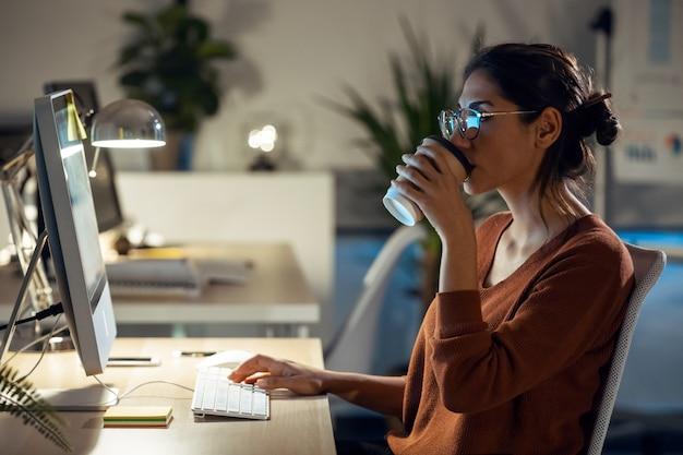 Schot van mooie jonge zakenvrouw die met de computer werkt terwijl ze koffie drinkt terwijl ze op kantoor zit.