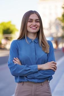 Schot van mooie jonge zakenvrouw draagt blauwe chifon shirt terwijl staande op straat met gevouwen armen.