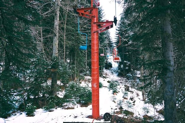 Schot van mooie oude kleine skilift met gekleurde stoelen, verplaatsen door winter woud in bergen