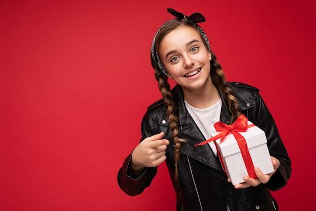 Schot van mooie positieve brunette kleine dame geïsoleerd over een rode achtergrondmuur die wit draagt