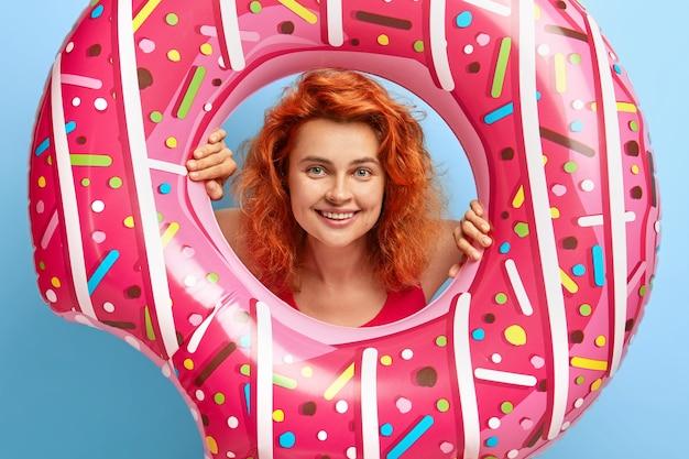 Schot van mooie vrolijke roodharige meisje kijkt door swimring gat