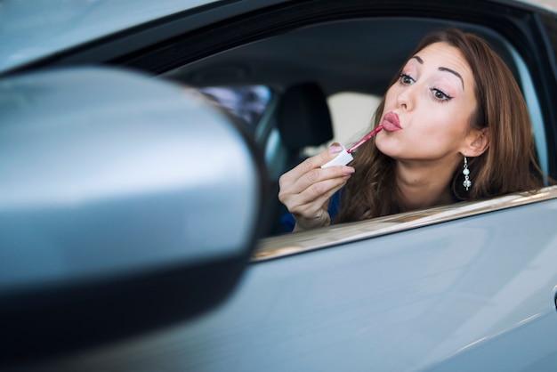 Schot van mooie vrouw bestuurder aanbrengen in haar auto achteruitkijkspiegel kijken en lippenstift zetten en make-up toe te passen
