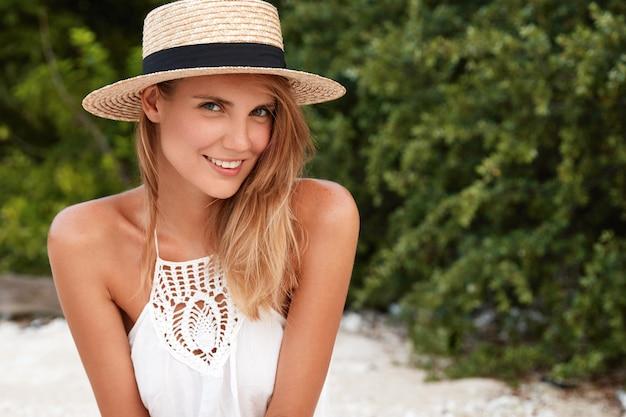 Schot van mooie vrouwelijke toerist recreëert op strand in tropisch land, heeft positieve uitdrukking, tevreden met goede rust en zomerweer. mensen, ontspanning, schoonheid en positieve uitingen