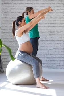 Schot van mooie zwangere vrouw met haar fysiotherapeut die pilates-oefeningen doet met bal die zich voorbereidt op de bevalling.