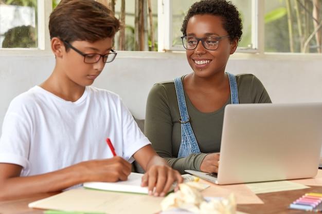 Schot van multi-etnische tiener studenten die betrokken zijn bij het werkproces, blader door informatie op draagbare laptopcomputer, schrijf ideeën voor projectwerk in kladblok, zit op het bureaublad, controleer het inkomstenbericht