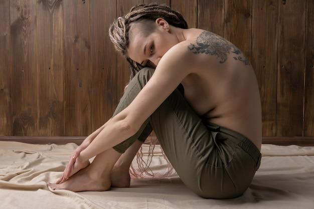 Schot van ongelukkige eenzame en depressieve jonge vrouw die haar gezicht tussen de benen thuis verbergt.
