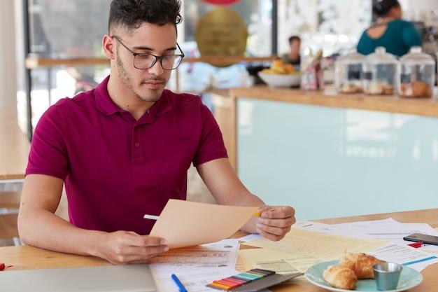 Schot van ongeschoren man onderzoekt papierwerk, gebruikt stickers, gekleed in casual t-shirt en bril. creatieve mannelijke blogger werkt met documentatie, heeft een harde werkdag, ontwikkelt een nieuwe strategie.