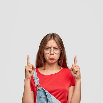 Schot van ontevredenheid mooie europese vrouw portretteert lippen van ongenoegen, gekleed in modieuze kleding, wijst naar boven met beide wijsvingers, houdt niet van iets. negatieve emoties concept