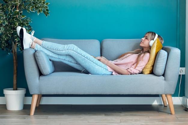Schot van ontspannen jonge vrouw die naar muziek luistert met smartphone terwijl ze thuis op de bank ligt.