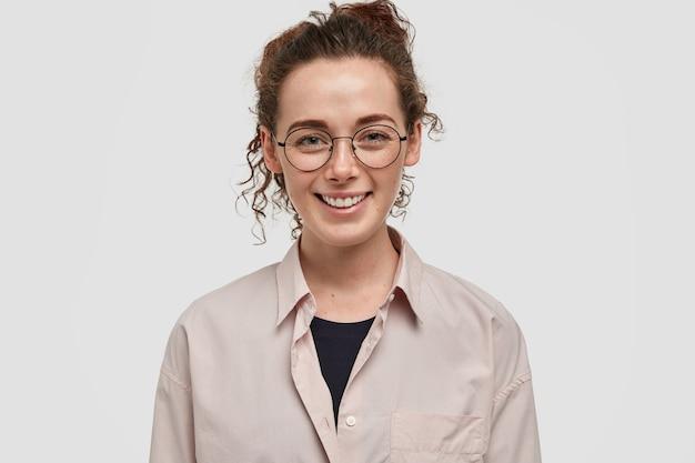 Schot van positieve europese jonge vrouw met donker krullend haar, zachte glimlach, sproeten huid heeft, draagt casual beige shirt