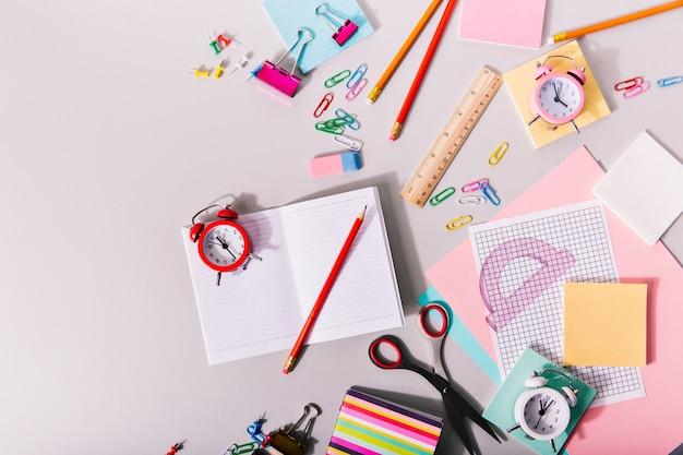 Schot van potloden, notitieboekjes en linialen van verschillende kleuren op de muur