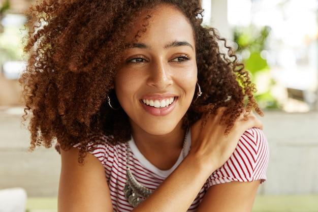 Schot van schattige mooie lachende vrouw met afro kapsel, gekleed in gestreept t-shirt, positieve en dromerige uitdrukking heeft, denkt over iets aangenaams. jonge vrouw met glanzende brede glimlach