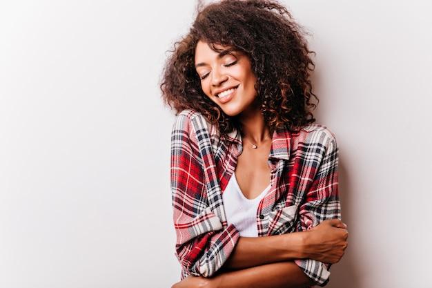 Schot van sensuele jonge afrikaanse vrouw. verbazend donkerbruin meisje in rood geruit overhemd dat met gesloten ogen lacht.