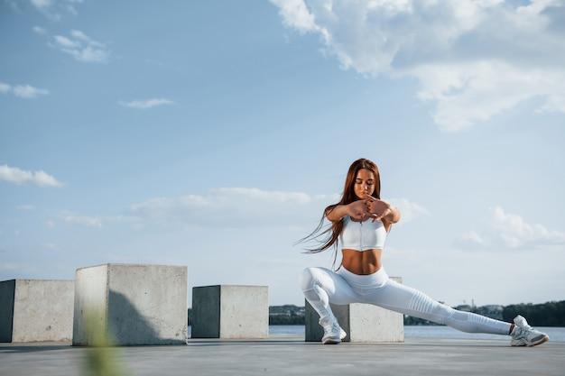 Schot van sportieve vrouw die overdag fitness doet in de buurt van het meer