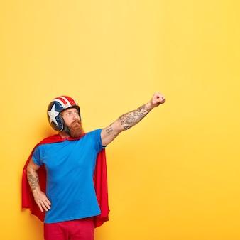 Schot van sterke man met ernstige uitdrukking, balde vuist en maakt vliegende gebaar, draagt helm