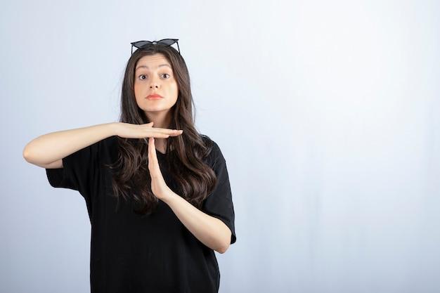 Schot van stijlvolle jonge vrouw poseren in zonnebril en time-out gebaar met handen tonen.