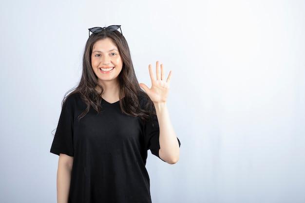Schot van stijlvolle lachende jonge vrouw poseren in zonnebril en nummer vijf met de hand tonen.