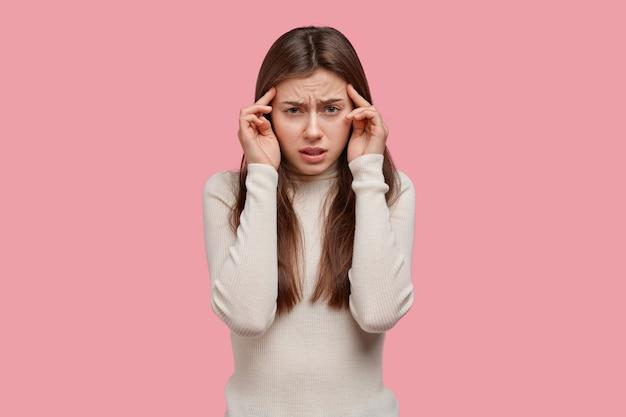 Schot van treurige jonge vrouw houdt vingers op slapen, heeft hoofdpijn, voelt zich uitgeput en ontevreden, probeert na te denken over het oplossen van het probleem