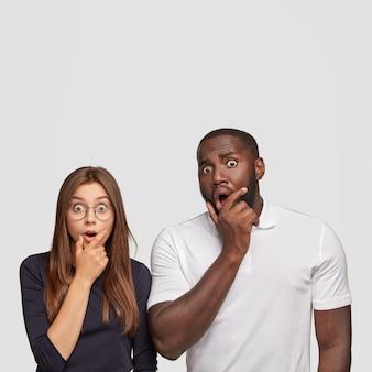 Schot van verbaasde partners van gemengd ras staren met ogen vol ongeloof, open mond, kunnen niet beseffen dat hun examen is mislukt